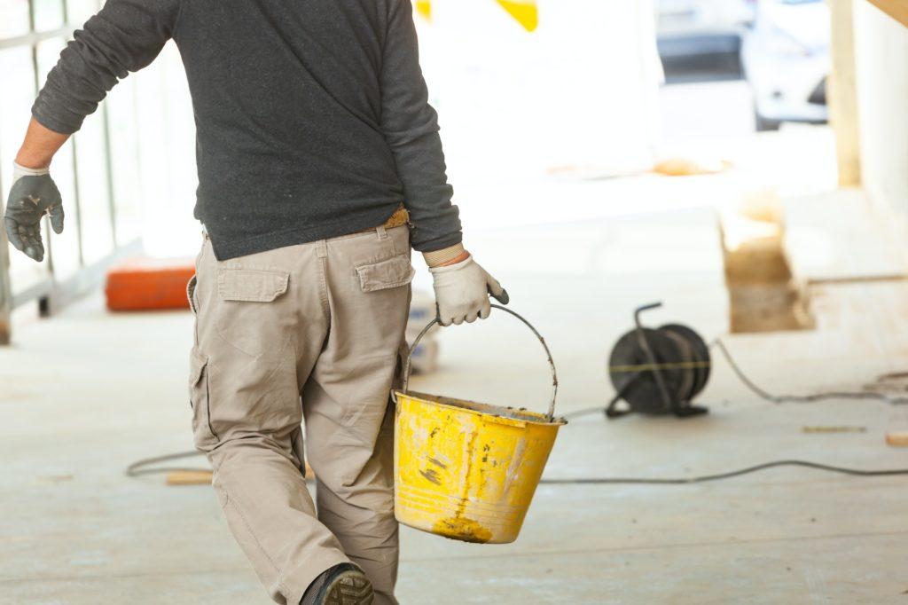 Trabajadora de construcción con mortero de cemento en obra.